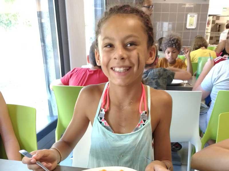 Enfant souriant qui mange en colonie de vacances