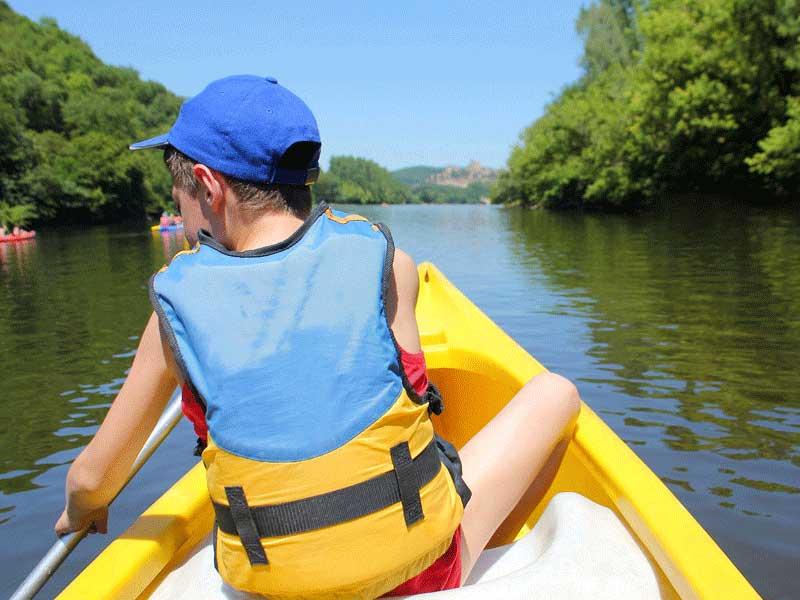 Enfant qui pratique le canoë en colonie de vacances