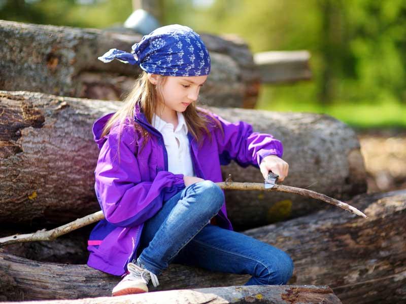 Enfant qui taille un morceau de bois