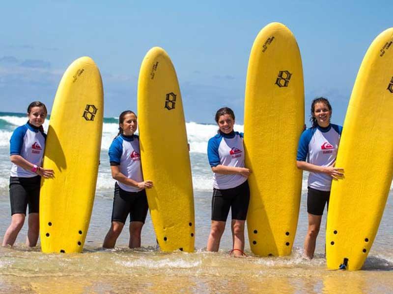 groupe d'ados avec leur planche de surf cet été