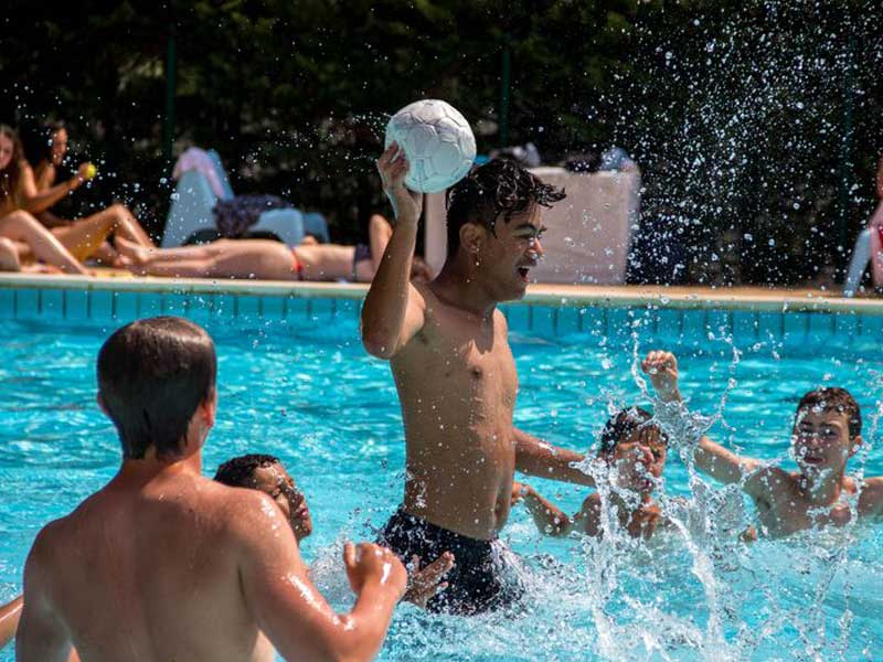 groupe d'ados jouant au ballon dans la piscine en colo cet été