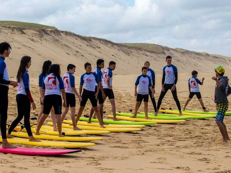 groupe d'ados avec leur planche de surf faisant des exercices cet été