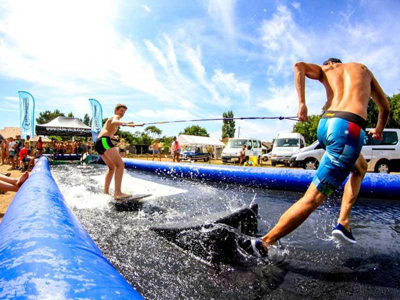 Enfants apprenant à faire du surf en colo cet été