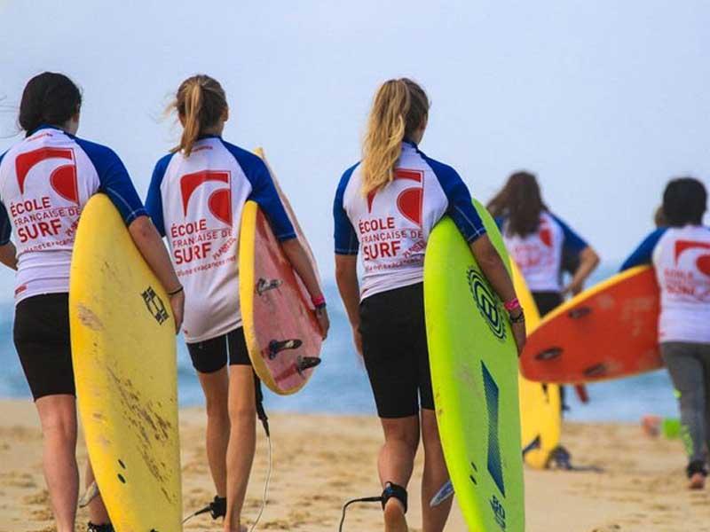 groupe d'ados avec leur planche de surf cet été en colo