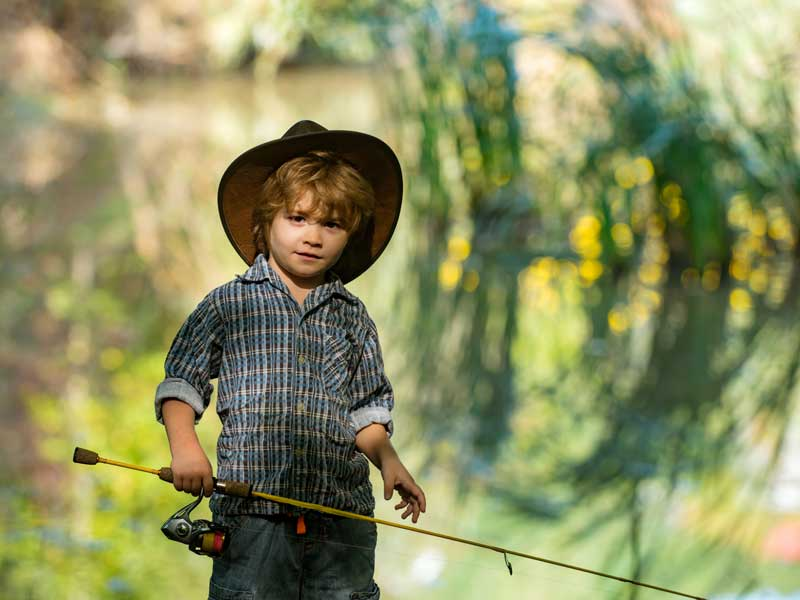 Enfant cow-boy en train de pécher en colonie de vacances