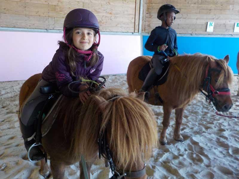 Deux enfants à cheval en colo l'été