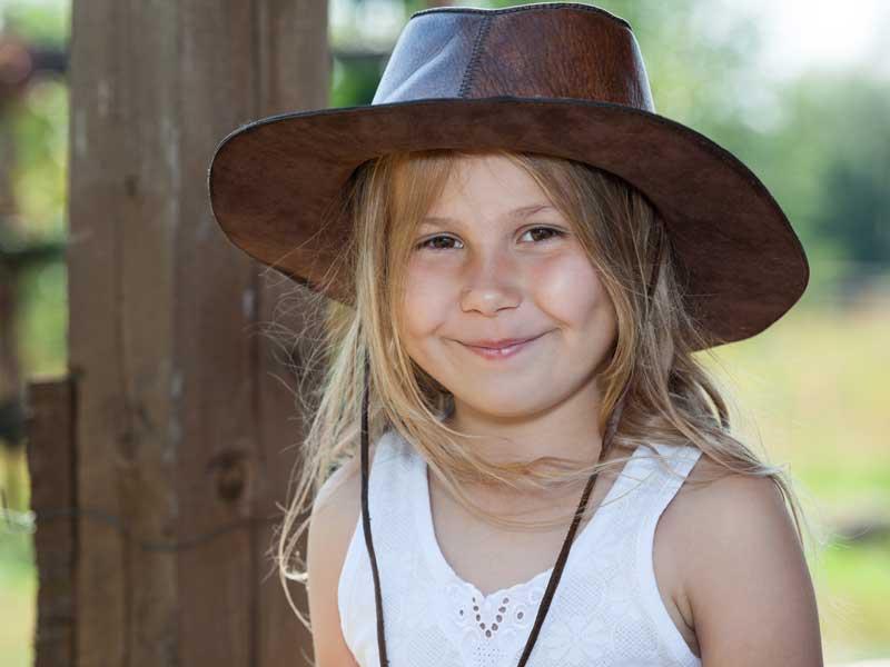 Petite fille qui souri avec un chapeau de cow-boy l'été