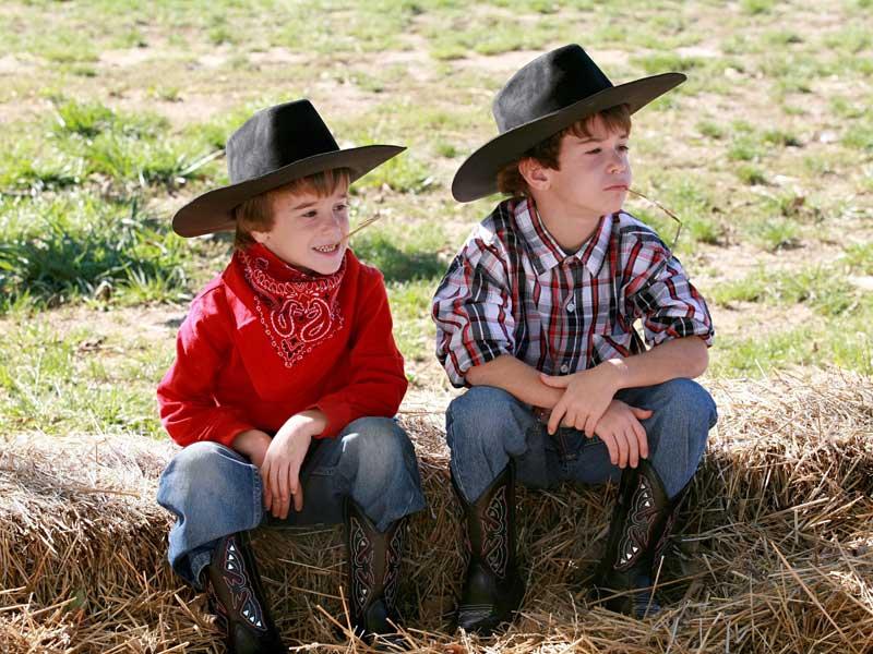 Deux garçons déguisés en cow-boys assis sur une botte de paille pour la colo d'été