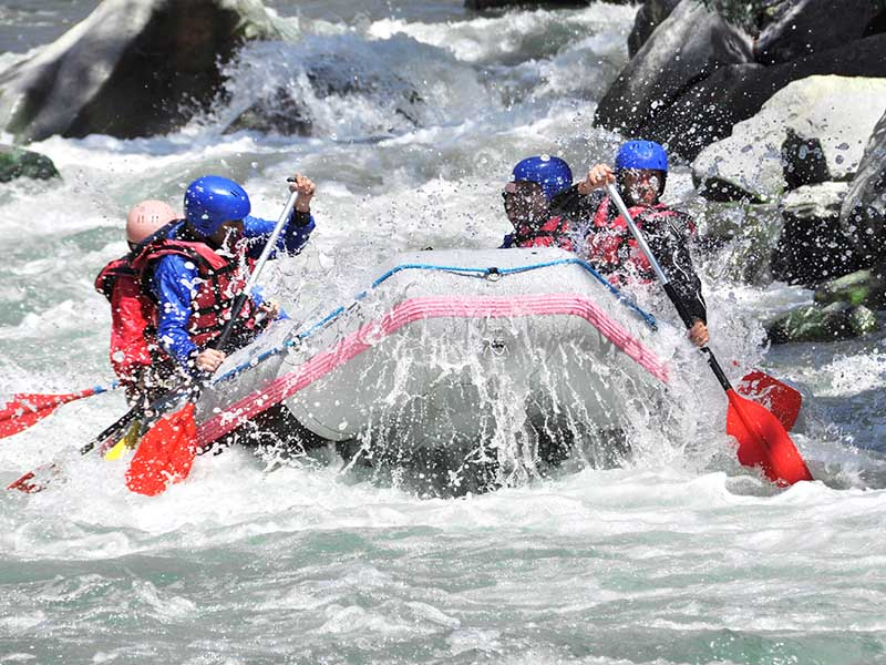 Groupe d'adolescent en colonie de vacances faisant une descente en rafting en été
