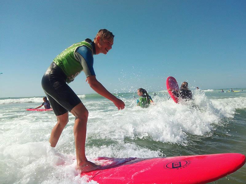 Un groupe d'adolescent fait du surf en colonie de vacances en été