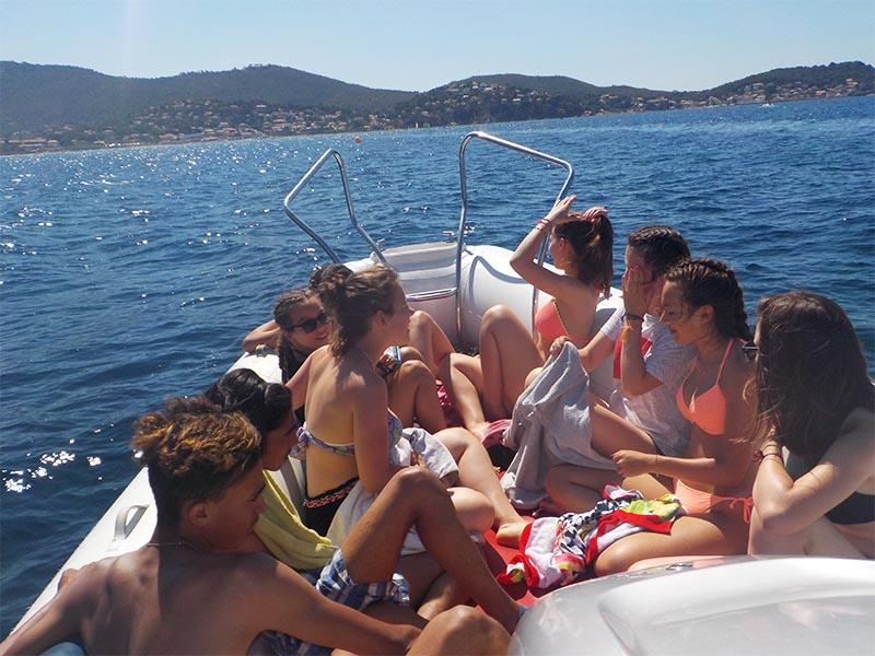 Un groupe d'adolescent en colonie de vacances en train de s'amuser sur un bateau au milieu de la mer en été