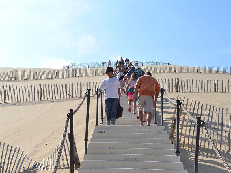 Un groupe de personne monte les marches de la Dune du Pilat en été