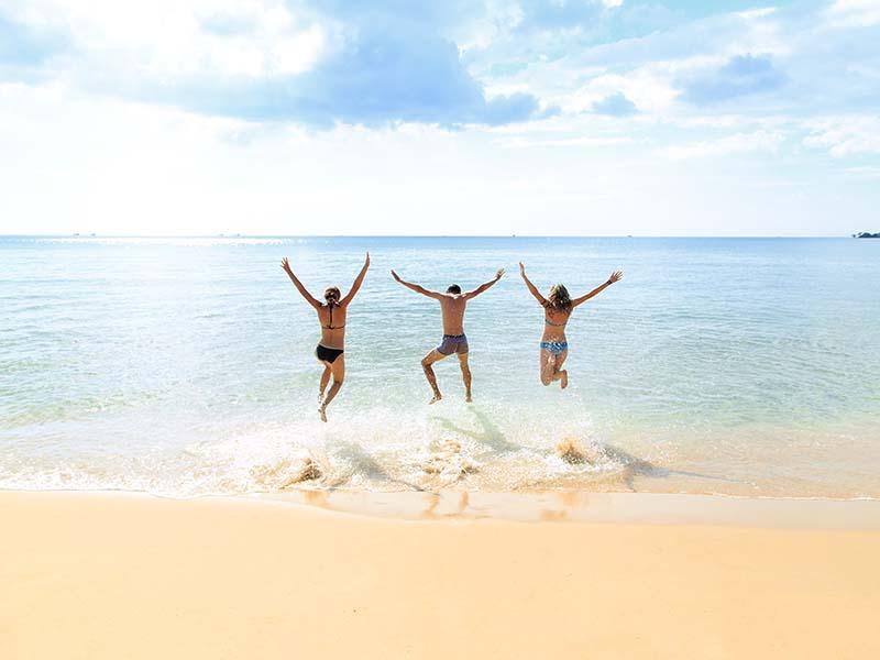 Trois jeunes en colonie de vacances, en été, sautent sur le sable pour éviter les vagues