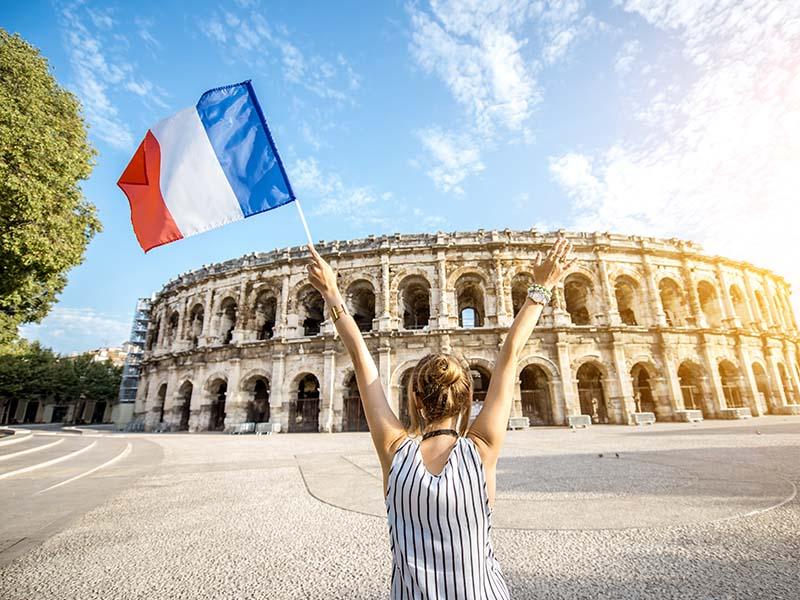 Un adolescent devant les Arènes de Nîmes, tenant dans la main un drapeau français en été