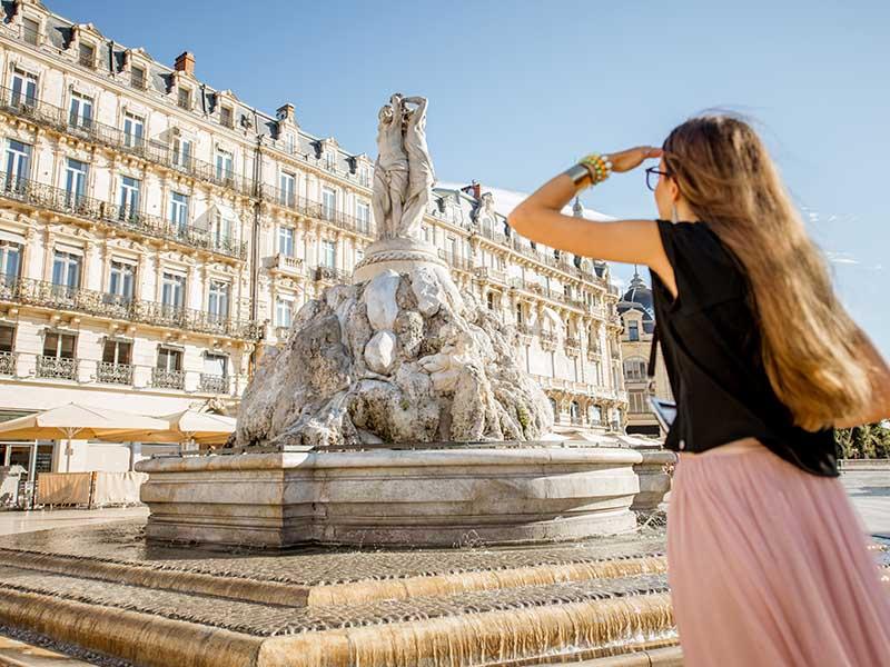 Une adolescente regarde la fontaine des Trois Grâces, place de la Comédie à Montpellier en été
