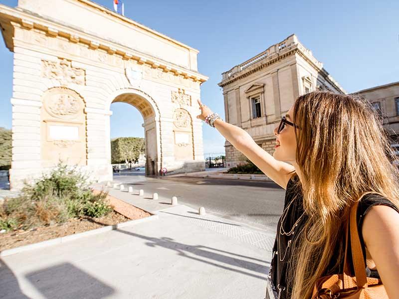 Une jeune fille pointe du doigt la porte du Peyrou de Montpellier