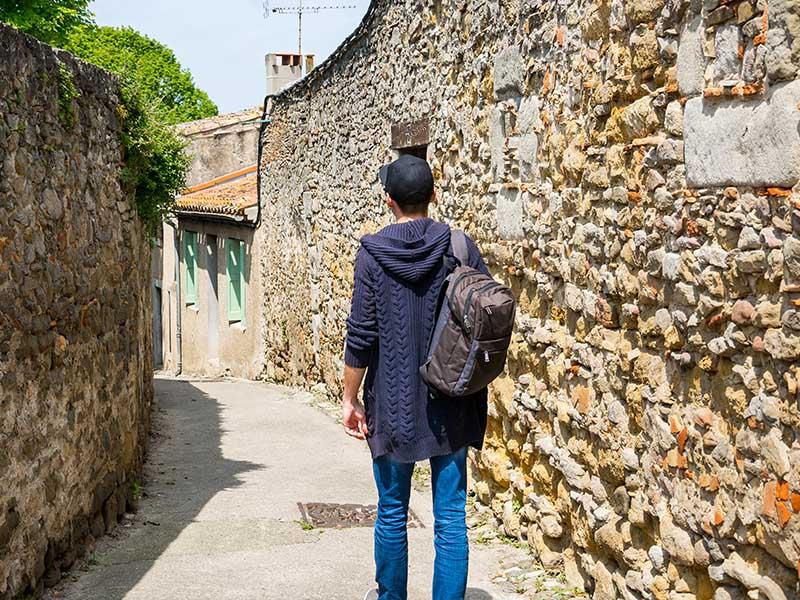 Un adolescent en colonie de vacances se balade dans les petites rues des villages d'Occitanie en été
