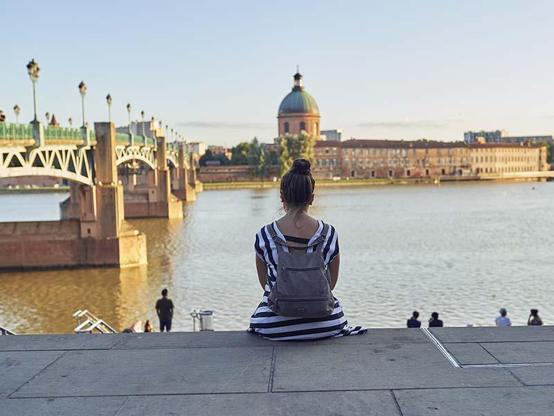 Une jeune fille se repose sur les marches des bords de la Garonne à Toulouse, en été
