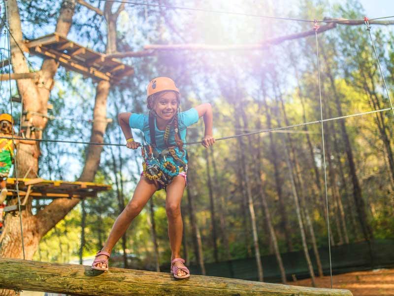 Jeune fille faisant de l'accrobranche en colonie de vacances