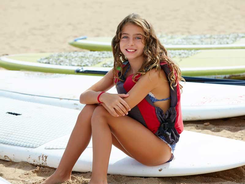 Jeune fille sur les planches de surf en colonie de vacances d'été