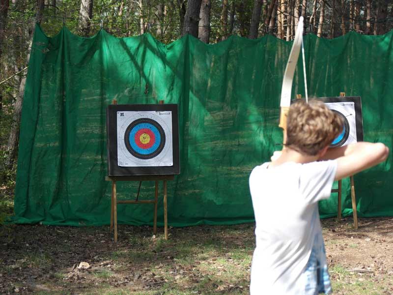 Enfant faisant du tir à l'arc en colonie de vacances d'été