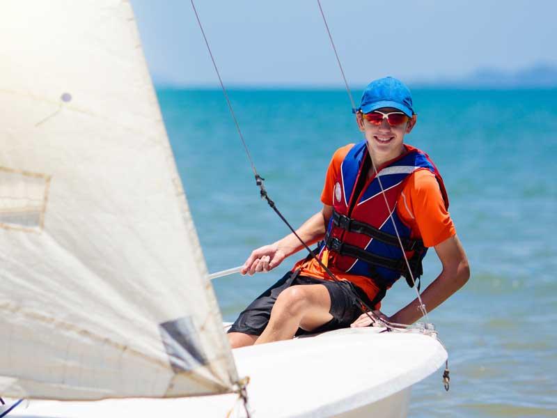 Enfant faisant de la voile en colonie de vacances à l'océan