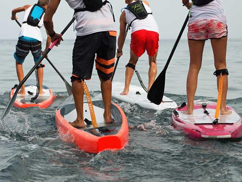 Enfants et ados faisant du paddle en colonie de vacances cet été