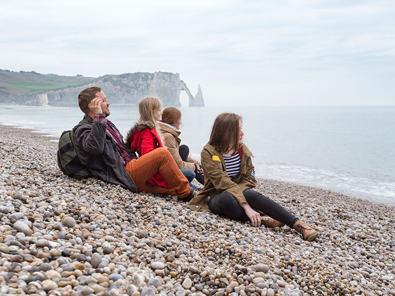 Un groupe d'adolescent en colonie de vacances assis sur une plage de galet en Bretagne en été
