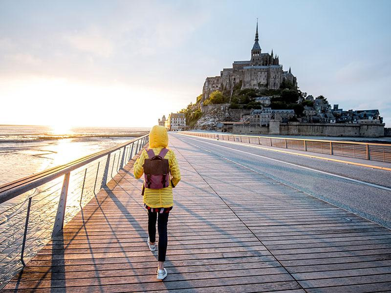 Une adolescente se promène devant le Mont-Saint-Michel en été