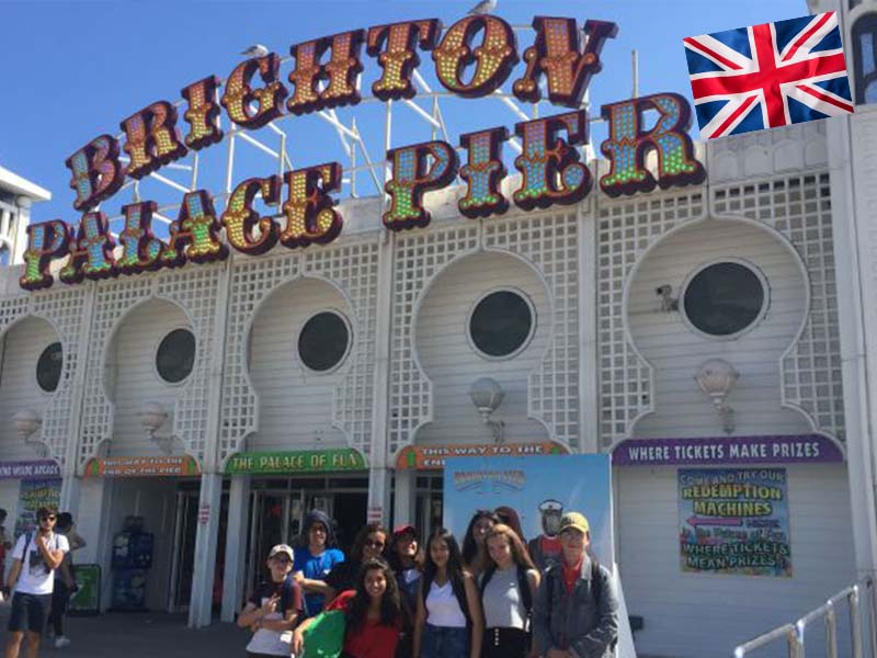 Groupe d'adolescent en colonie de vacances devant le Brighton Palace Pier en Angleterre