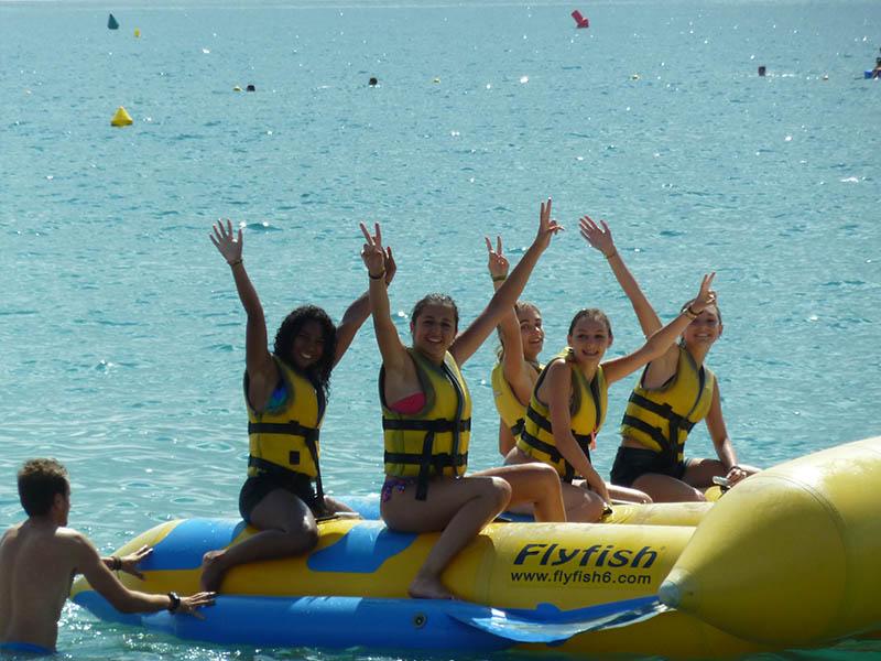 Groupe de jeunes faisant de la bouée tractée en colonie de vacances cet été