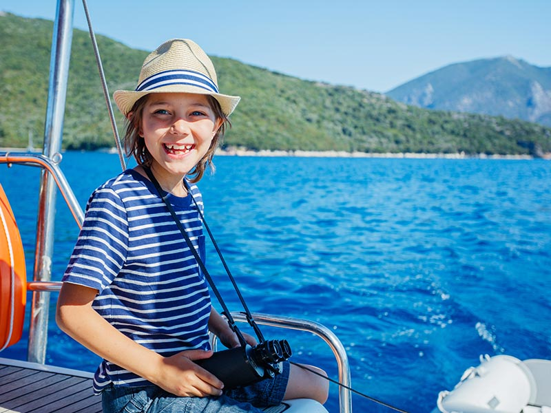 Enfant en balade à bateau en colonie de vacances à la mer