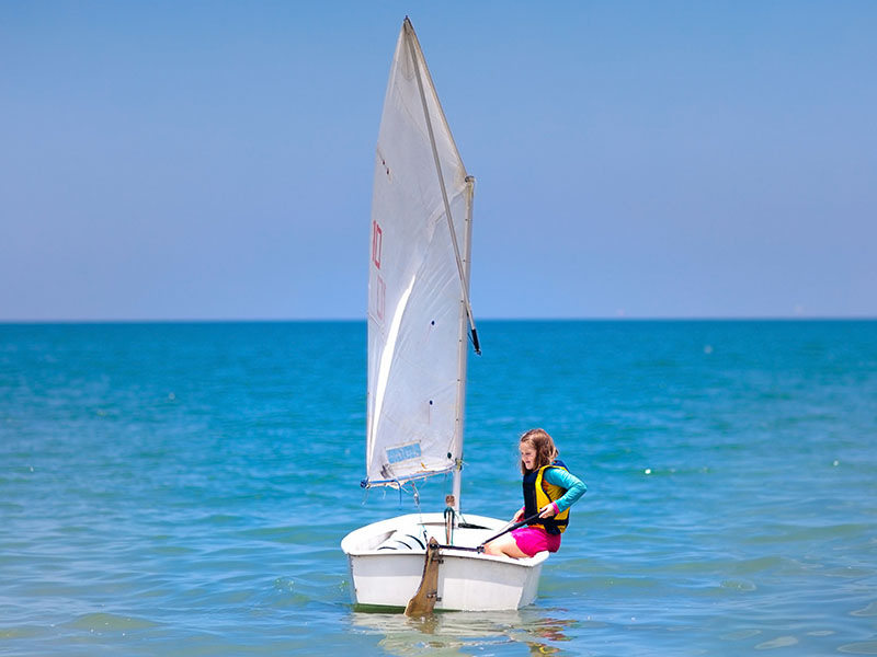 Fillette apprenant à faire de l'optimist en colonie de vacances cet été
