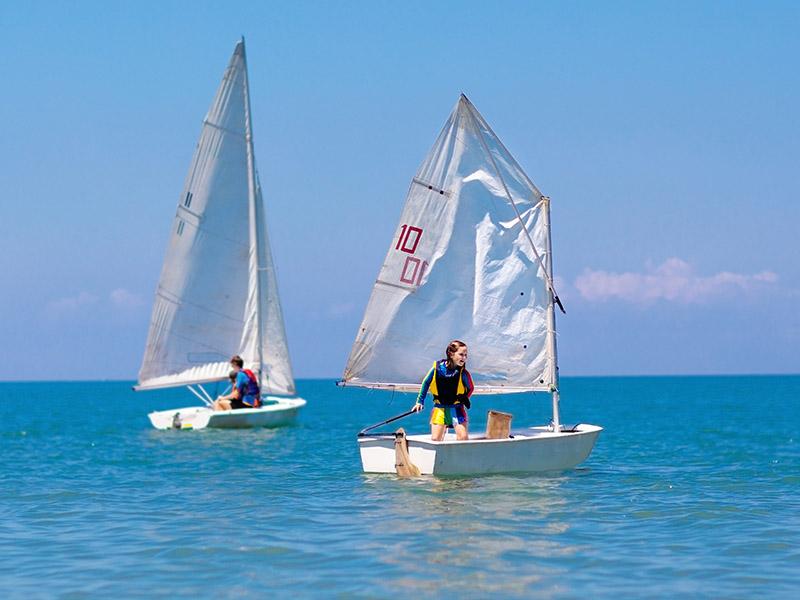 Enfants faisant de l'optimist en colo cet été à la mer