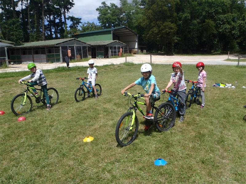 Enfants faisant du vélo en colo cet été