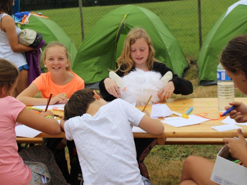 Enfants écrivant des lettres à leurs parents en colonie de vacances cet été
