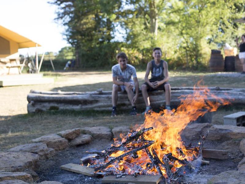 Adolescents autour du feu de camp cet été en colo