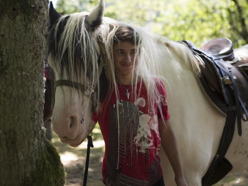 portrait d'un jeune ado avec son cheval en colo