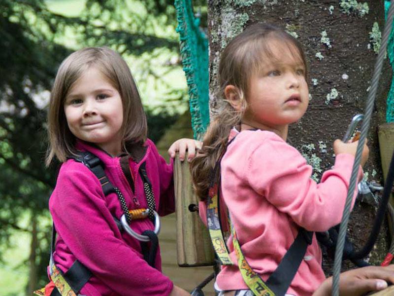 deux fillettes faisant de l'accrobranche en colonie de vacances cet été