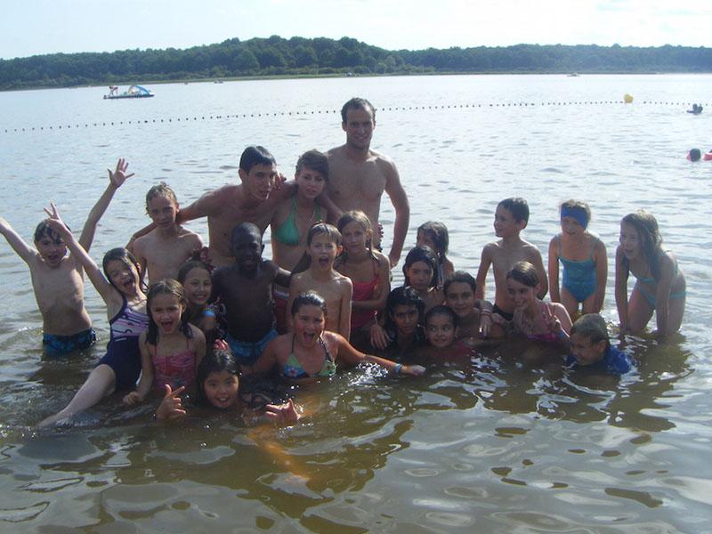 groupe d'ados et enfants se baignant au lac en colonie de vacances