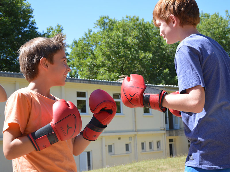 deux jeunes faisant de la boxe en colo pour apprendre langlais