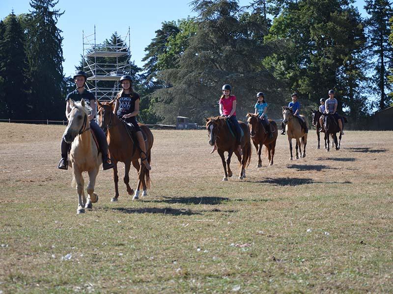 groupe d'ados à cheval en balade cet été lors d'une colo pour apprendre l'anglais