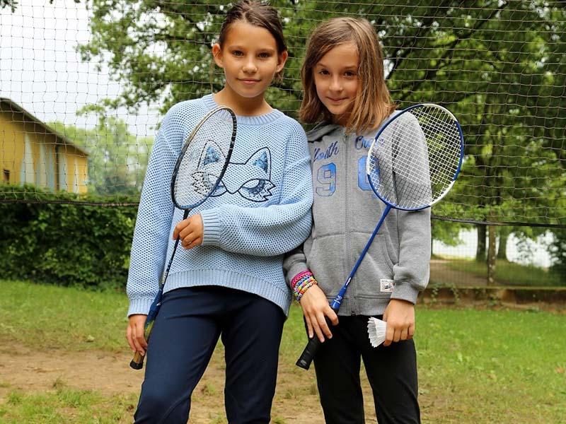 deux jeunes filles avec des raquettes de badminton en colonie de vacances cet été