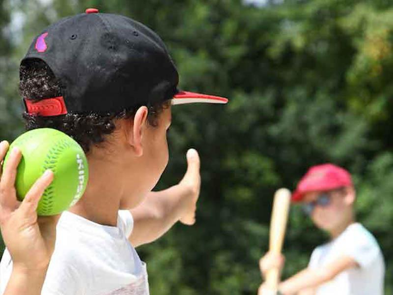 enfant lancant une balle de baseball en colonie de vacances cet été