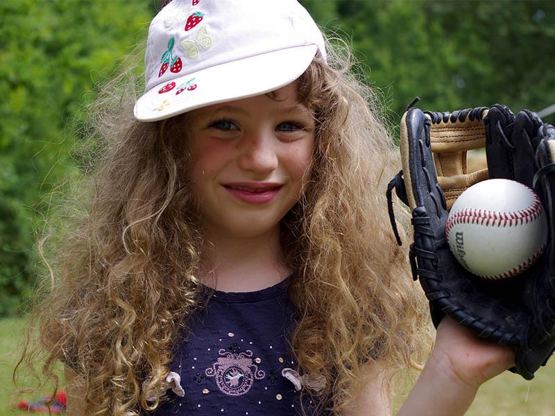 Fillette tenant une balle de baseball en colonie de vacances anglaise cet été