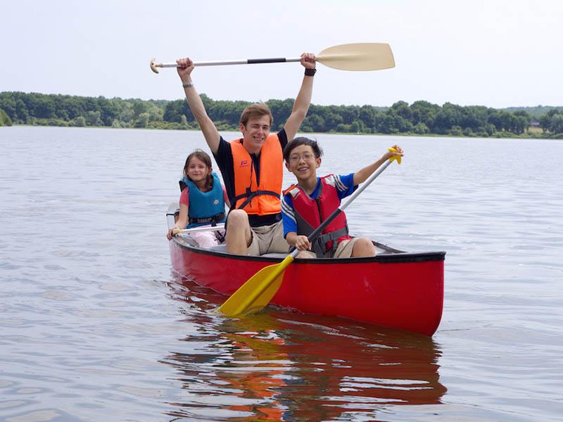 enfants faisant une balade en barque en colonie de vacances cet été