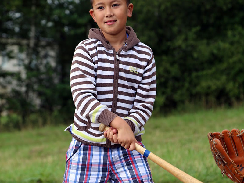 enfant apprenant à faire du baseball en colonie de vacances cet été