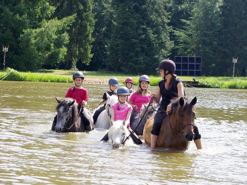 adolescents faisant de l'équitation dans le lac en colonie de vacances cet été