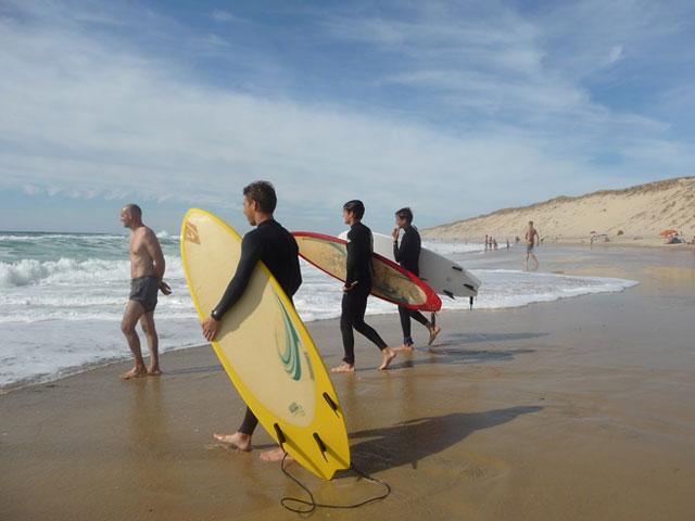 adolescents avec leur planche de surf au bord de l'eau en colonie de vacances d'été