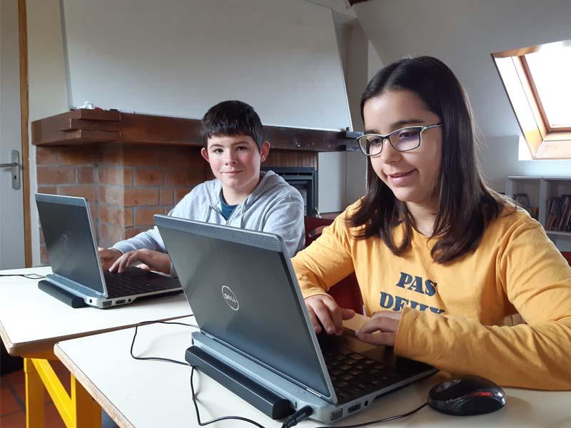 Deux jeunes enfants en colonie de vacances cet été sur un ordinateur